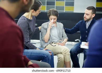 Friendly colleagues reassuring their groupmate in tears at session