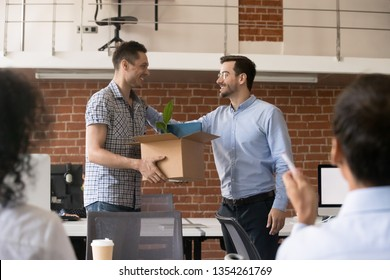 Friendly company ceo welcoming new male employee holding cardboard box with belongings in hands, first day at work, team welcoming new member, newcomer, getting acquainted with coworkers, introduction