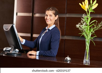 Friendly concierge at hotel reception behind the counter