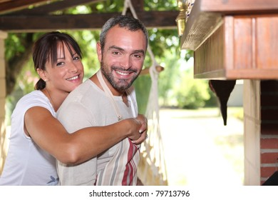Friendly couple standing by the barbecue