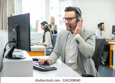 Friendly customer support agent with headset working in call center.