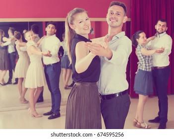 Friendly dancing couples enjoying foxtrot in dance studio