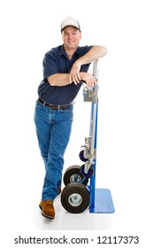 Friendly delivery man leaning against his hand truck.  Full body isolated on white.