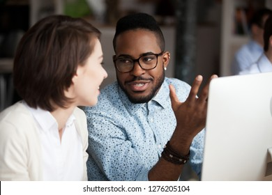 Friendly diverse colleagues having conversation in office, creative african american and caucasian workers discussing work chatting, black male worker talking to female coworker collaboration concept