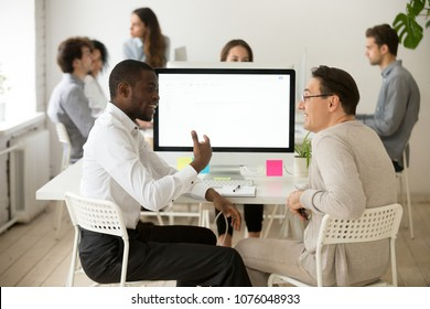 Friendly diverse colleagues having good relations and pleasant conversation at work, smiling african and caucasian coworkers talking in office, multiracial team members discussing new project idea