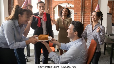 Friendly diverse employees in party hats presenting birthday cake congratulating male colleague boss, multicultural workers make surprise to coworker laughing and having fun at corporate celebration