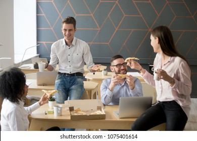 Friendly diverse team talking and laughing eating pizza together, happy colleagues sharing meal, multiracial coworkers group enjoying lunch at break, good relations and office food delivery concept
