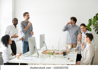 Friendly diverse work team having fun, laughing while eating pizza and Asian food from takeaway delivery, talking and joking, colleagues enjoy spending time together during lunch break
