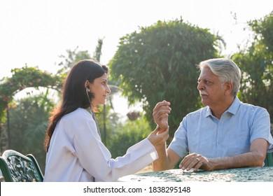 Friendly doctor taking care of senior man in the hospital garden