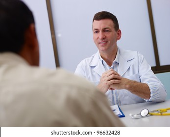 Friendly doctor working and giving assistance to old male patient in hospital office. Focus on background