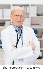 Friendly elderly male doctor with a stethoscope around his neck standing with folded arms in his office or surgery smiling at the camera