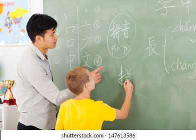 friendly elementary school teacher helping young boy writing chinese on chalkboard