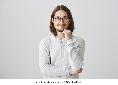 Friendly employer pleased with great ideas of his team. Interested positive handsome guy with beard and long hair wearing stylish glasses, holding hand on chin, smiling, expressing curiosity