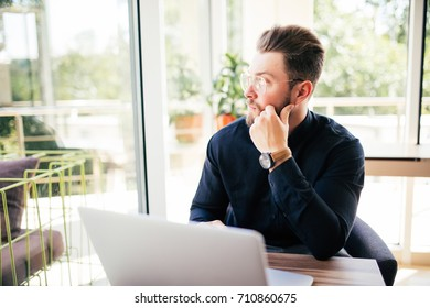 Friendly executive sitting in front of laptop in his office. Big window at the background.