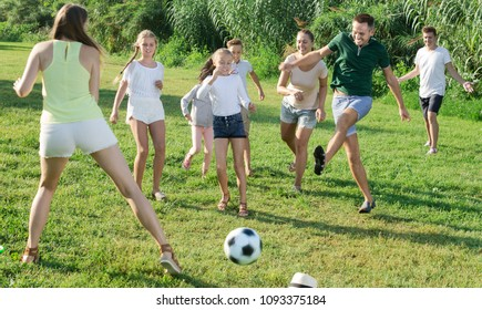 Friendly family with children having fun together outdoors playing football