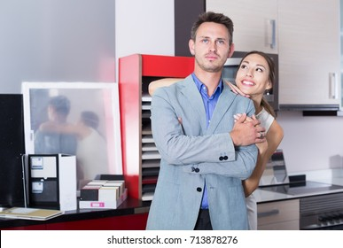 Friendly family couple looking at modern kitchen  in store