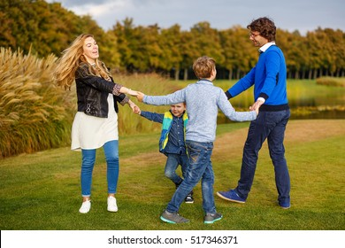 Friendly family: mother, father and two sons dancing in a beautiful park. They are dressed in casual clothes.