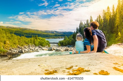A friendly family is resting sitting on the rock of a cascading waterfall of a crystal clear mountain river. Surrounded by beautiful mountains and sunlight.