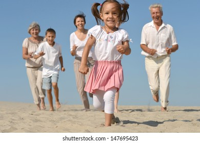 friendly family running for a little girl on the sand