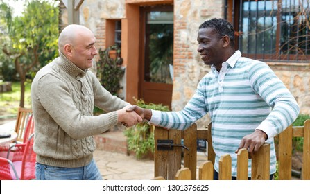 Friendly farmer greeting his neighbor on courtyard of rural house, shaking hand