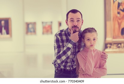 friendly father and daughter regarding paintings in halls of museum