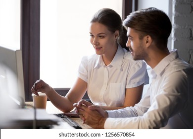 Friendly female advisor business mentor teacher training male new employee consult client with computer explaining work to intern, corporate colleagues talking in office, help and discussion concept