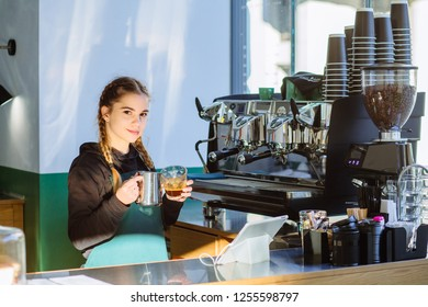 Friendly female barista adding milk to coffee. Making coffee in a professional way ,espresso with milk, coffee latte art in coffee shop make by barista.