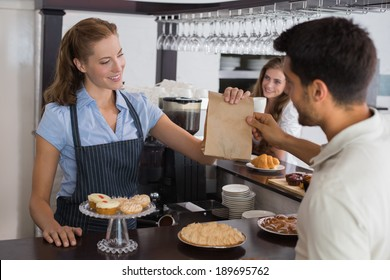 Friendly female cafe owner giving packed food to a couple at the coffee shop