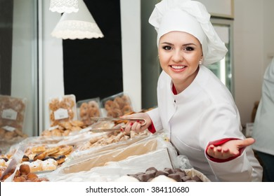 Friendly female with cook hat staff offering tasty pastry in local confectionery