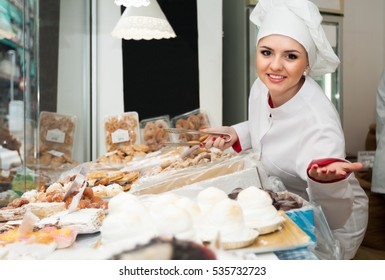 Friendly female with cook hat staff offering pastry in local confectionery