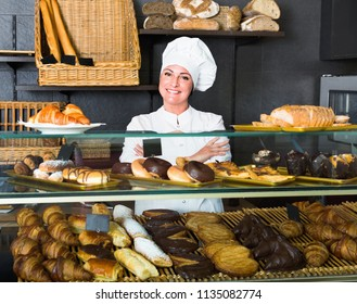Friendly female cooks demonstrating and selling to the customer pastry in the cafe counter
