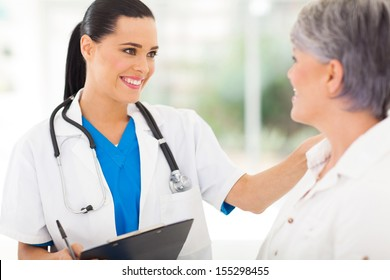 friendly female doctor comforting middle aged patient in hospital