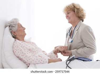 Friendly female doctor comforting a senior patient at hospital or retirement house