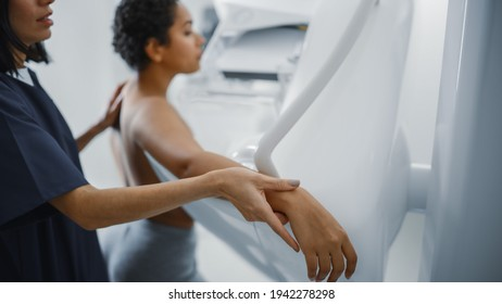 Friendly Female Doctor Explains the Mammogram Procedure to a Topless Latin Female Patient with Curly Hair Undergoing Mammography Scan. Healthy Female Does Cancer Prevention Routine in Hospital Room.