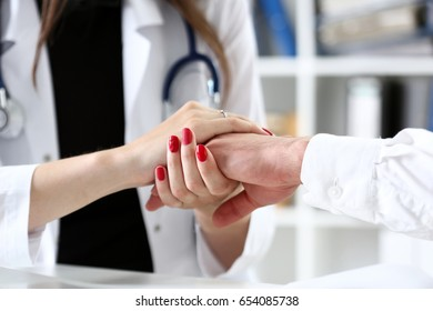 Friendly female doctor hold male patient hand in office during reception.