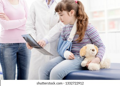 Friendly female doctor showing an x-ray image to a young patient with broken arm, healthcare and children concept
