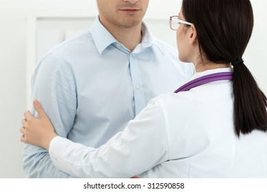 Friendly female doctor touching male patient's arm for encouragement and empathy. Partnership, trust and medical ethics concept. Bad news lessening and support. Patient cheering and support