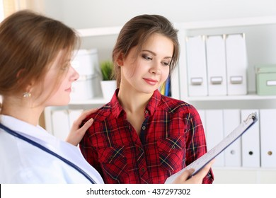 Friendly female doctor touching patient shoulder for encouragement, empathy, cheering and support after medical examination. Trust and ethics concept. Good news, healthcare and medical service concept