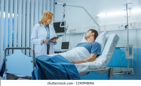 Friendly Female Doctor Visits Happy Recovering Man who is Lying in Bed, She Asks Him Questions and Fills Medical Chart. Friendly Doctor and Sick Man in a Clean Hospital Ward.