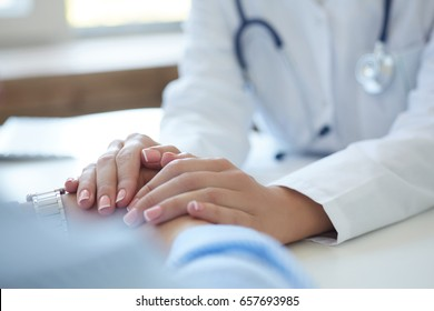 Friendly female doctor's hands holding male patient's hand for encouragement and empathy. Partnership, trust and medical ethics concept. Bad news lessening and support.