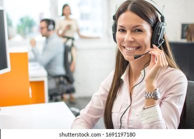 Freundlicher weiblicher Helplinenbetreiber mit Kopfhörern im Callcenter