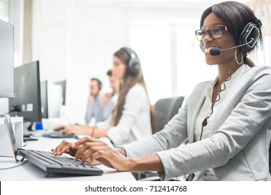 Friendly female helpline operator with headphones in office. Agent customer service representative: business and office concept.
