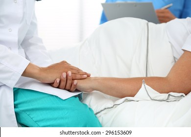 Friendly female medicine doctor's hands holding pregnant woman's hand lying in bed for encouragement, empathy, cheering and support while medical examination. New life of abortion concept