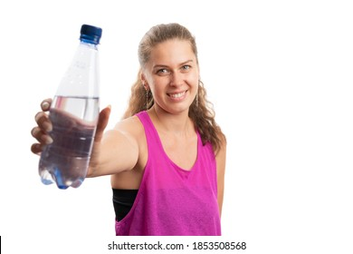 Friendly fit female model wearing pink tanktop sportswear smiling as presenting water bottle as healthy hydration post-workout concept isolated on white studio background