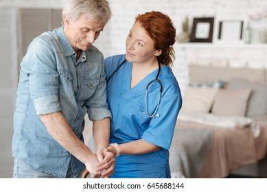 Friendly focused nurse encouraging her elderly patient
