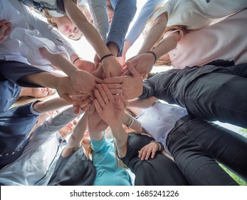 Friendly friends join hands as a sign of joint business. The concept of team and community.
