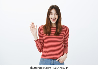 Friendly girl saying hi to best friends. Portrait of cheerful bright european woman in striped pullover, waving hand in hello gesture and smiling broadly, pleased to see familiar person on street