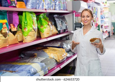 Friendly girl seller showing different types of food for pets in pet shop