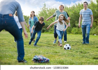 Friendly and glad family playing football and scoring goals
