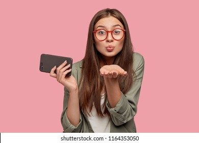 Friendly gorgeous lady blows air kiss at camera, holds modern cell phone, says good bye on distance, poses against pink background. Cute woman in eyewear flirs with boyfriend, uses cellular.